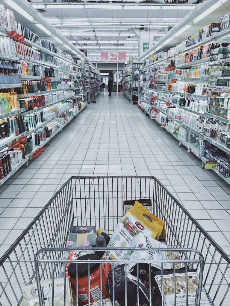 gambar troli di tengah rak supermarket