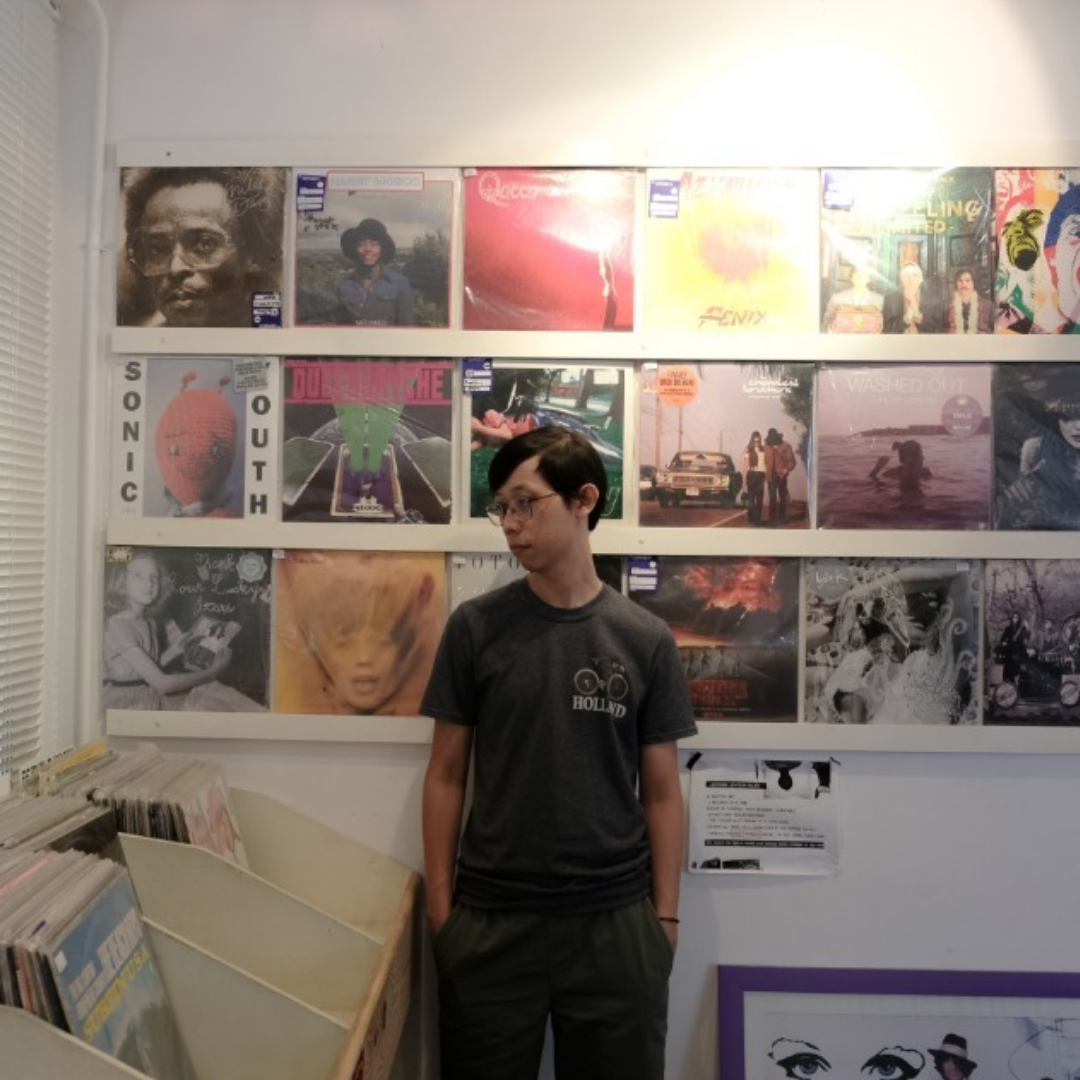 Nelson berpose di depan dinding cover vinyl