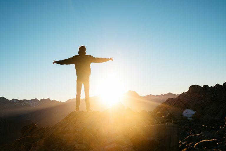 seseorang berdiri merentangkan tangan di atas gunung menghadap matahari