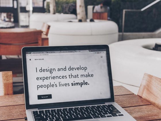 """Laptop di meja kayu yang bertuliskan website """"I design and develop experience that make people life's simpler."""